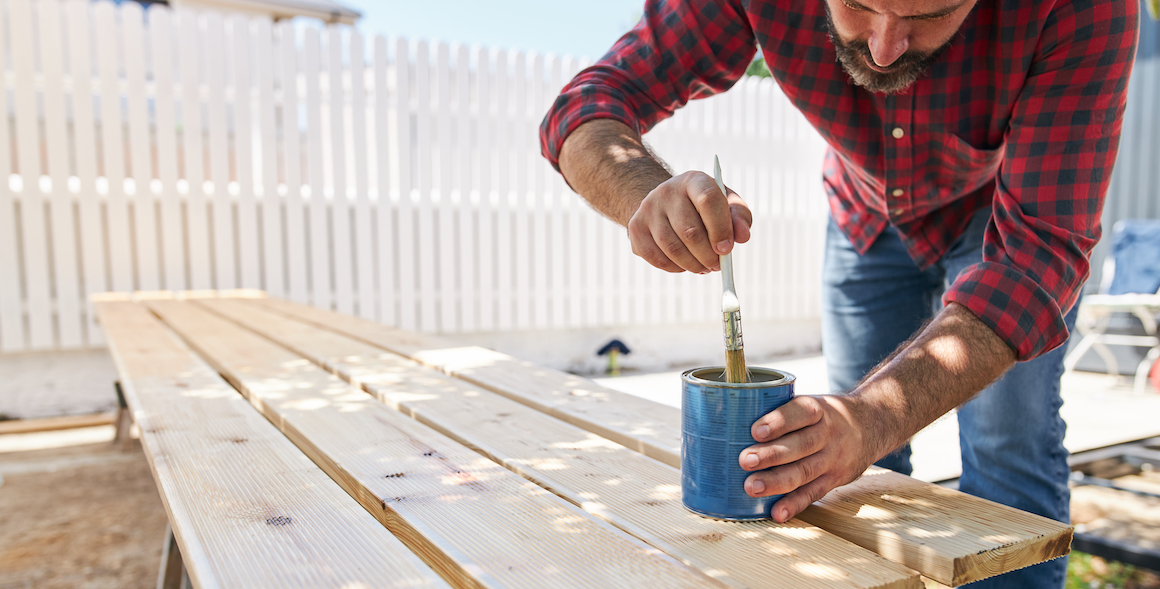 iQ member painting wooden boards for home repair