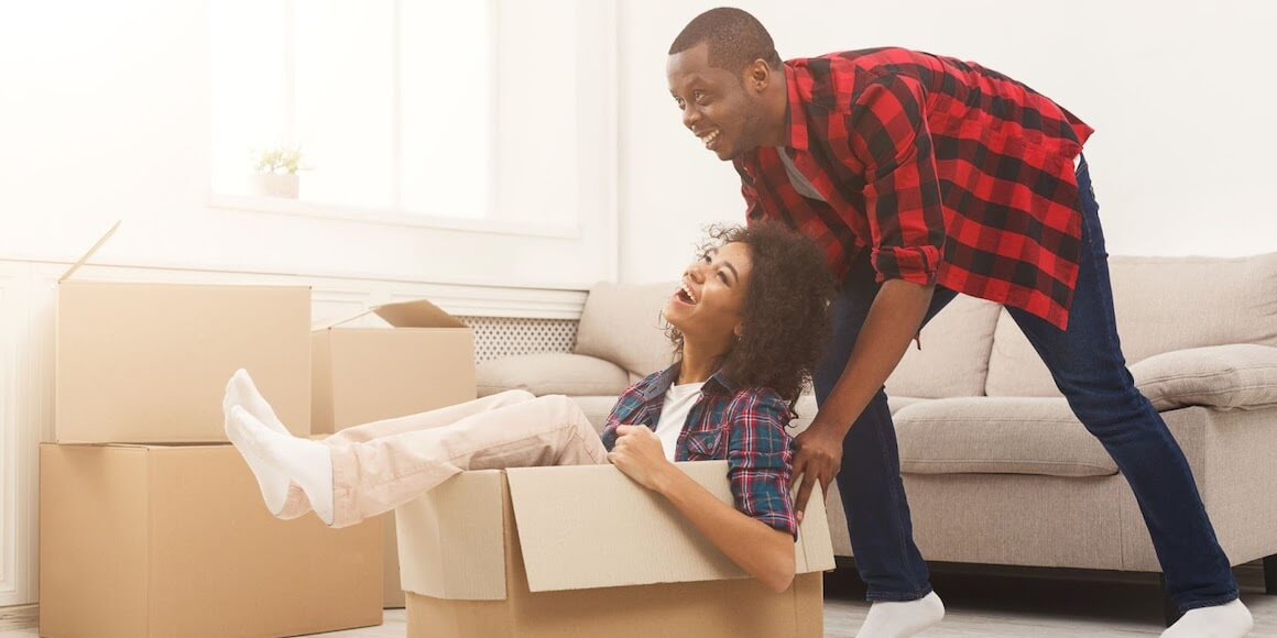Husband and wife playing with boxes moving into a new home