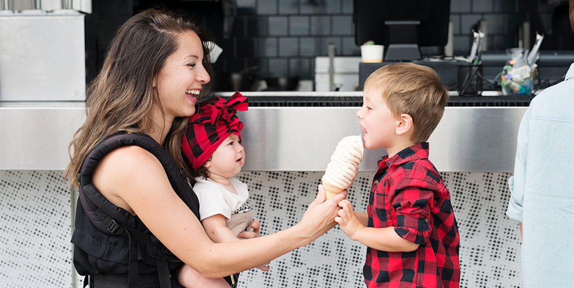 Mother sharing ice cream with her two children